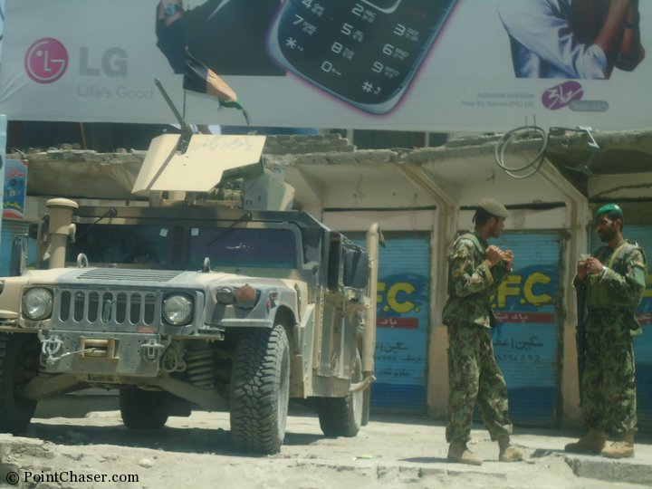 Afghan soldiers chatting near an unmanned tank