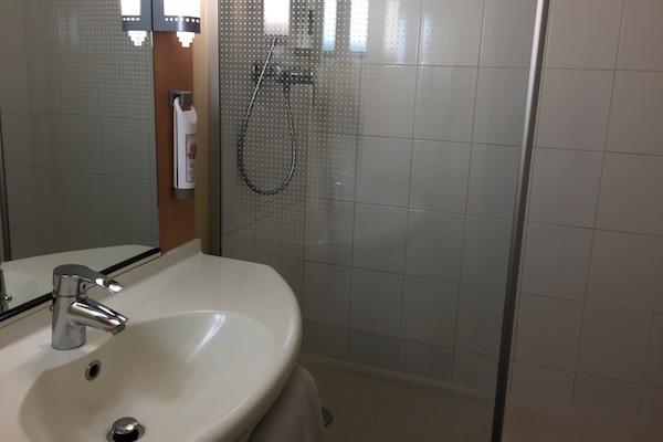 Bathroom sink and shower at Ibis Calais Hotel